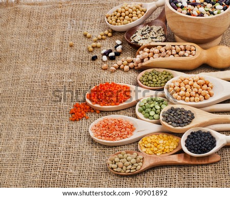 various food ingredients : beans, legumes, peas, lentils in wooden spoon on the sackcloth background - stock photo