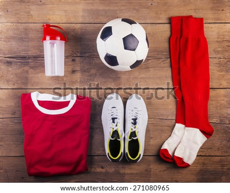 Various football stuff lined up on a wooden floor background - stock photo