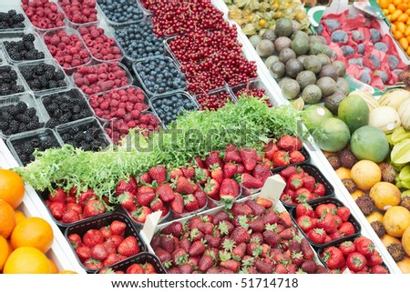 Various fresh berries on food market stall - stock photo