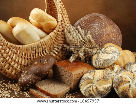 Various fresh crispy baked goods with a basket, wheat grain, poppy and a cereal ears - stock photo