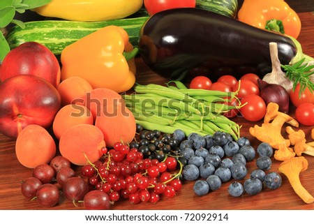 Various fresh fruits and vegetables on a wooden table - stock photo