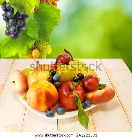 various fresh fruits on a plate on a green background - stock photo