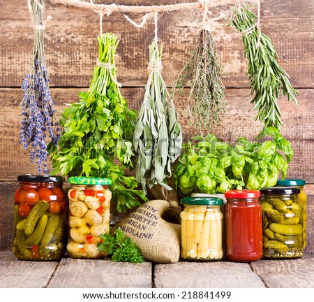 various fresh herbs and canned food on wooden background - stock photo