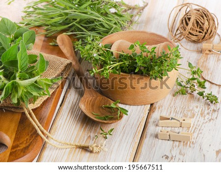 Various fresh herbs on a wooden table . Selective focus