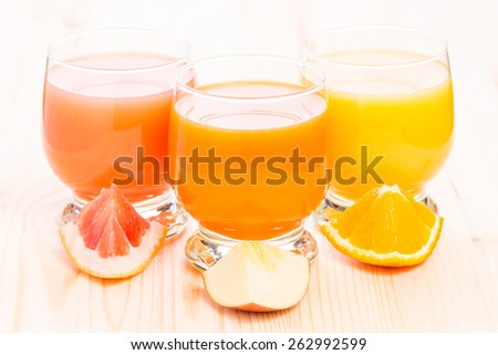 Various fresh juice in glass on wooden table. Healthy organic beverages with pieces of fruit. Vitamins background - stock photo