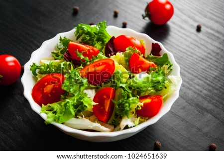 various fresh mix salad leaves with tomato in bowl on dark wooden background