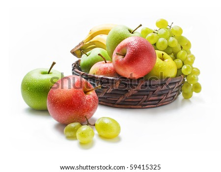 Various fresh ripe fruits placed in a wicker basket and around isolated on a white background - stock photo