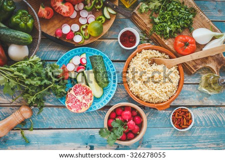 Various fresh vegetables on a blue wooden table  and cook burghul in ceramic bowl ready to prepare arabian traditional food. Country food concept from above. Series. - stock photo
