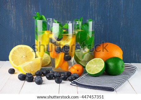Various fresh vitamin flavored fruit infused water in glasses with fruits and napkin on white wooden table against blue colored wall. - stock photo