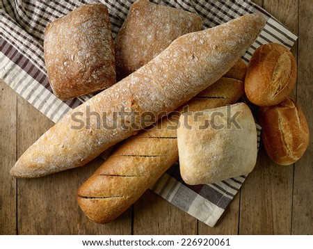 various freshly baked bread buns on old wooden table - stock photo