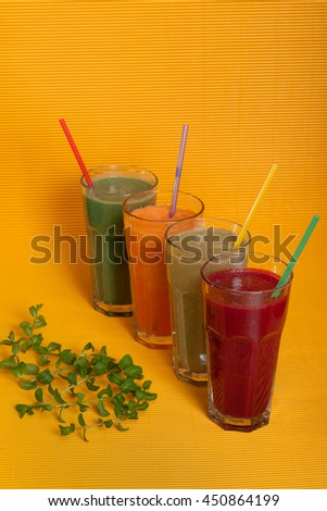 Various freshly squeezed vegetable juices on yellow background. - stock photo