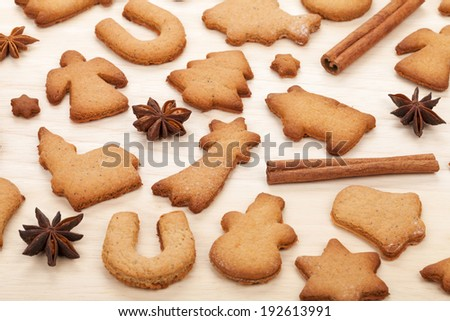 Various gingerbread cookies with spices on wooden table background