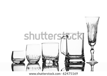 Various glass glasses on a white background with reflexion - stock photo