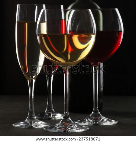 Various glasses of red and white wine with abstract pattern and bottle on black wooden background. - stock photo