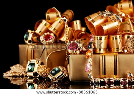Various gold jewellery and gifts on black background - stock photo