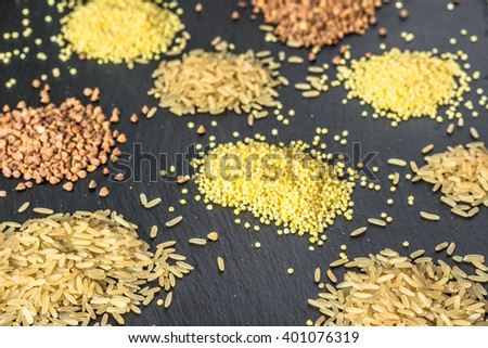 Various grain of cereal - rice, millet buckwheat on black  background, selective focus - stock photo
