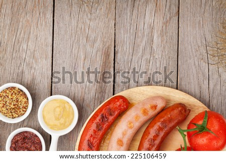 Various grilled sausages with condiments and tomatoes on cutting board with copy space - stock photo