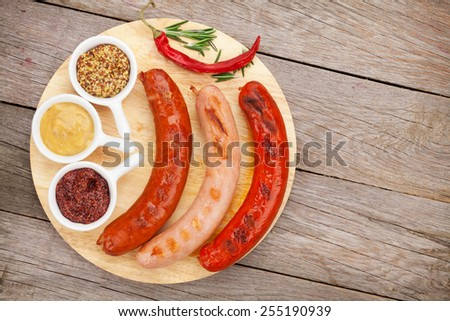 Various grilled sausages with condiments on cutting board with copy space - stock photo
