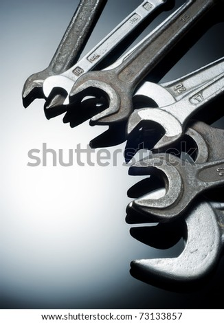 Various hand wrenches on black glass board with copy space.