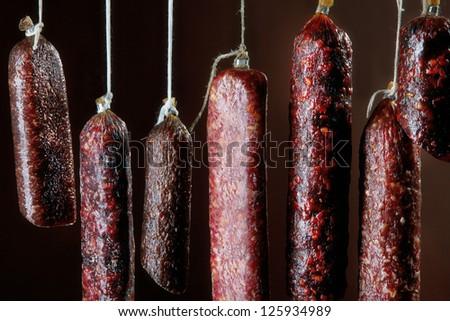 various hanging salami sausages - stock photo