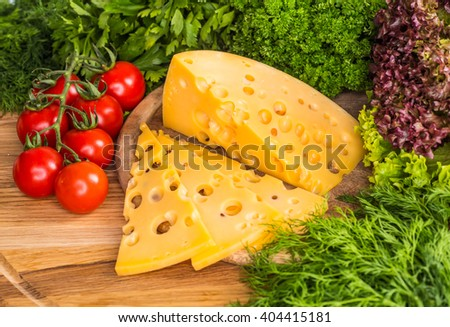 Various hard cheeses served on a wooden board. - stock photo