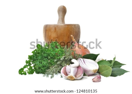 various herbs and onions and garlic with a wooden pestle isolated - stock photo