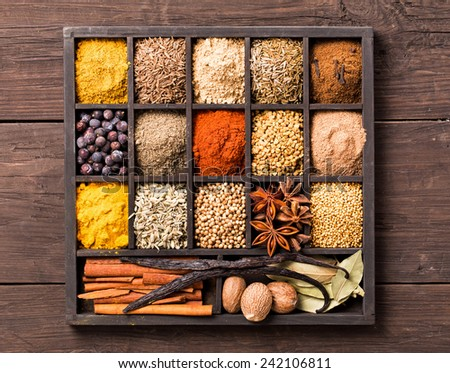 Various herbs and powder spices in box on old wooden background top view - stock photo