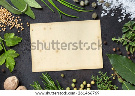 various herbs arranged as a frame on a dark metal tray, paper scrap with copyspace for your text