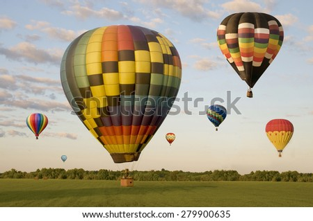 Various hot-air balloons landing in a field. One is on the ground. Others are floating. - stock photo
