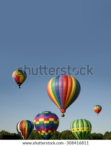 Various hot-air balloons with colorful envelopes ascending or launching at a ballooning festival - stock photo