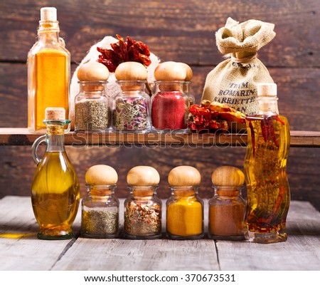 various jars of dried spices on wooden background