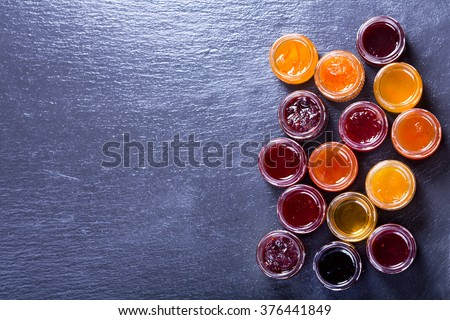 various jars of fruit jam on dark background - stock photo