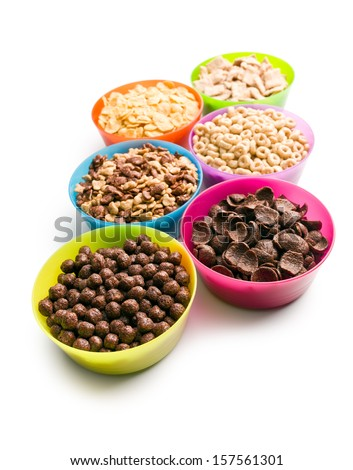 various kids cereals in plastic bowls on white background - stock photo