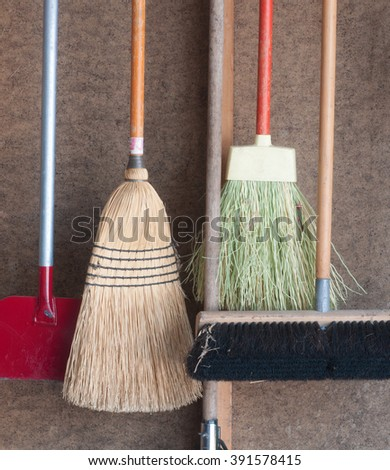 Various kind of brooms and a sidewalk ice scraper hanging on pegboard wall in the garage - stock photo