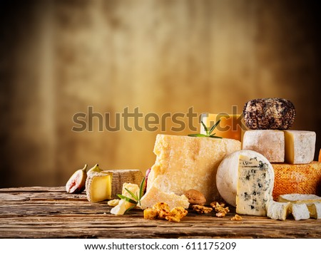 Various kind of cheese served on wooden table, traditional pieces of french and italy hand-made cheese. Copyspace for text