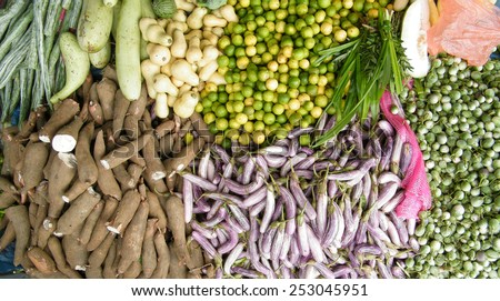 Various kind of fresh green vegetables (Egg plant, Brinjol, limes, cucumber,manioc) at market - stock photo