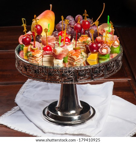 Various kinds of canapes with cheese, meat, fish, fruits and vegetables - stock photo