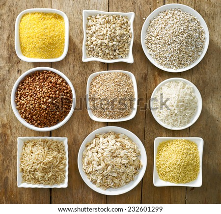 various kinds of cereal grains on old wooden table - stock photo
