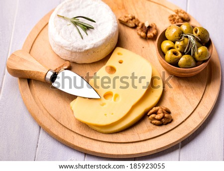 Various kinds of cheese and olives on wooden plate - stock photo