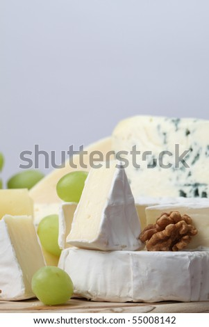 Various kinds of cheese with walnuts and grapes - stock photo