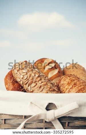 Various kinds of fresh tasty bread in wicker basket. Shallow depth of field, vintage style. - stock photo