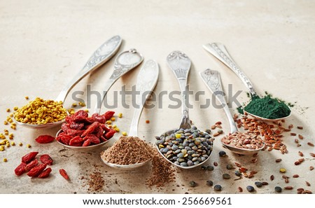 various kinds of healthy superfood seeds in silver spoons, top view - stock photo