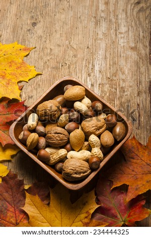 various kinds of nuts in wooden bowl with copy space - stock photo