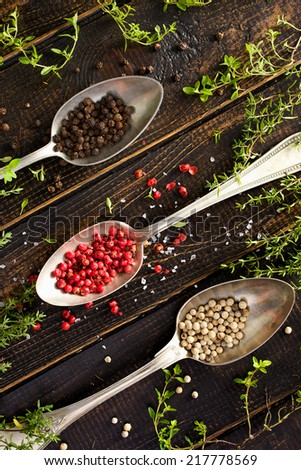 Various kinds of pepper and fresh thyme - stock photo