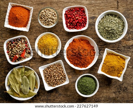 various kinds of spices on wooden table - stock photo