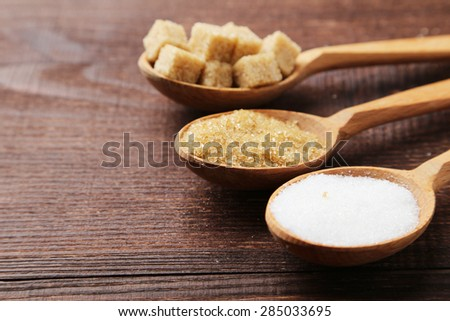 Various kinds of sugar in spoons on brown wooden background - stock photo