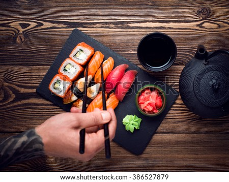 Various kinds of sushi served on black stone. Sushi Set sashimi and sushi rolls, top view - stock photo