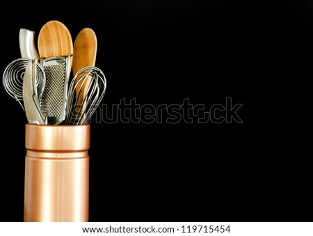 Various kitchen tools in a ceramic container on a black background