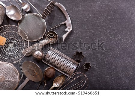 Various kitchen utensils on dark background, top view with copy space