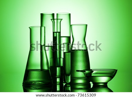 various laboratory glasses, beakers and test tubes in green light